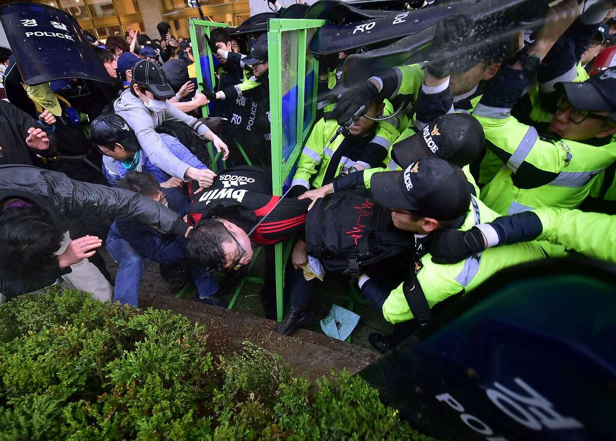 South Korean protestors clash with riot police during a rally to commemorate the first anniversary of the Sewol ferry disaster in Seoul on April 18, 2015. Hundreds of protestors clashed with police in Seoul on April 18 after families of the victims of South Korea's ferry disaster were prevented from marching to the president's residence.