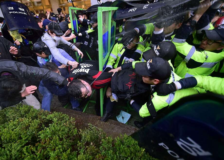 South Korean protestors clash with riot police during a rally to commemorate the first anniversary of the Sewol ferry disaster in Seoul on April 18, 2015. Hundreds of protestors clashed with police in Seoul on April 18 after families of the victims of South Korea's ferry disaster were prevented from marching to the president's residence. Photo: Jung Yeon-je, AFP / Getty Images