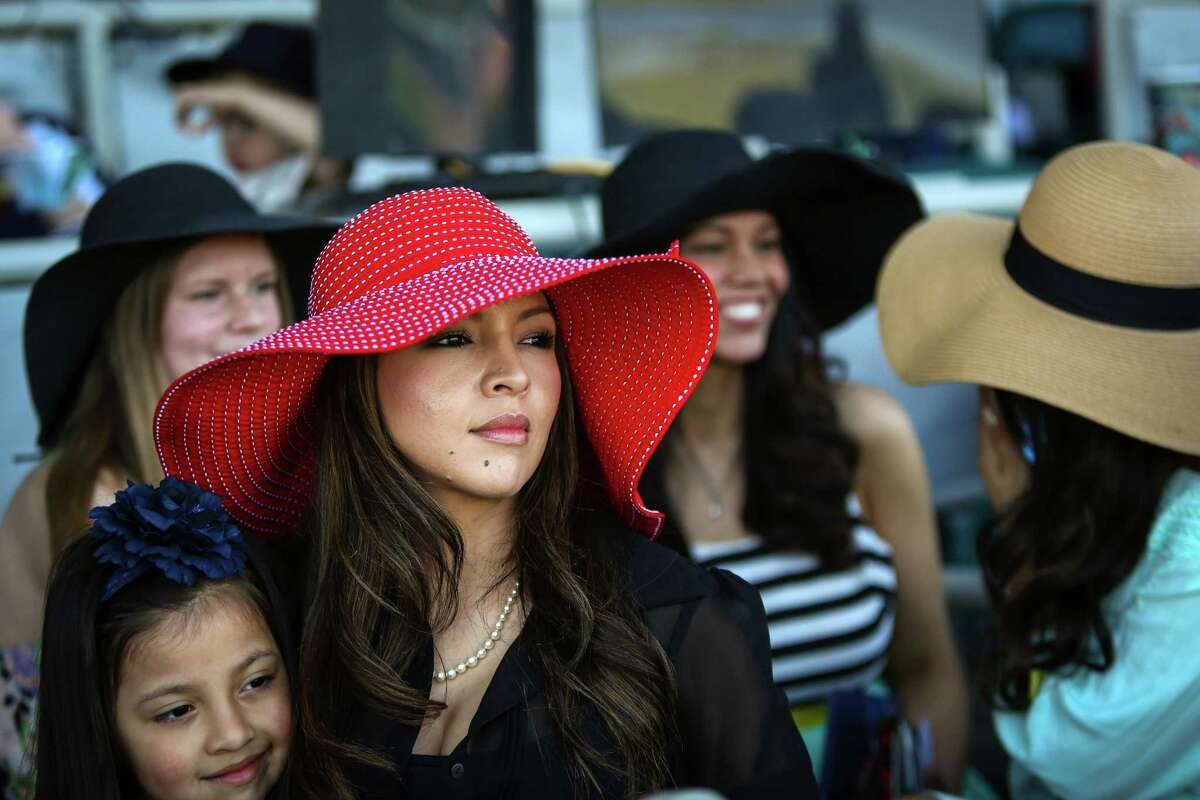 Diana Roldan holds her daughter Mikaela, 5, as horses run during the opening day of the 20th Emerald Downs racing season on Saturday, April 18, 2015. Hats are a big part of opening day at Emerald Downs. The local racing season kicked off at the track in Auburn with a crystal clear view of Mount Rainier as a backdrop.