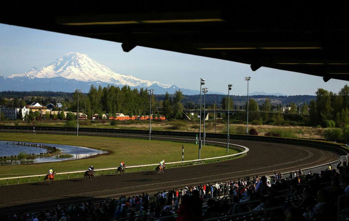 Horses run during the opening day of the 20th Emerald Downs racing season on Saturday, April 18, 2015. The local racing season kicked off at the track in Auburn with a crystal clear view of Mount Rainier as a backdrop.