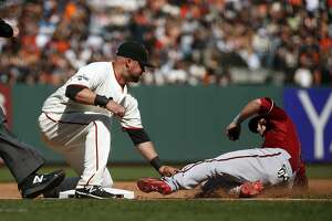 San Francisco Giants' Casey McGehee tags out Arizona Diamondbacks' Chris Owings after a failed sacrifice attempt by Nick Ahmed in 9th inning of Diamondbacks' 5-1 win during MLB game at AT&T Park in San Francisco, Calif., on Sunday, April 19, 2015.