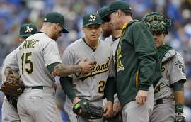 Oakland Athletics starting pitcher Scott Kazmir, center, is taken from a baseball game by manager Bob Melvin, second from right, during the eighth inning against the Kansas City Royals at Kauffman Stadium in Kansas City, Mo., Sunday, April 19, 2015. (AP Photo/Orlin Wagner)