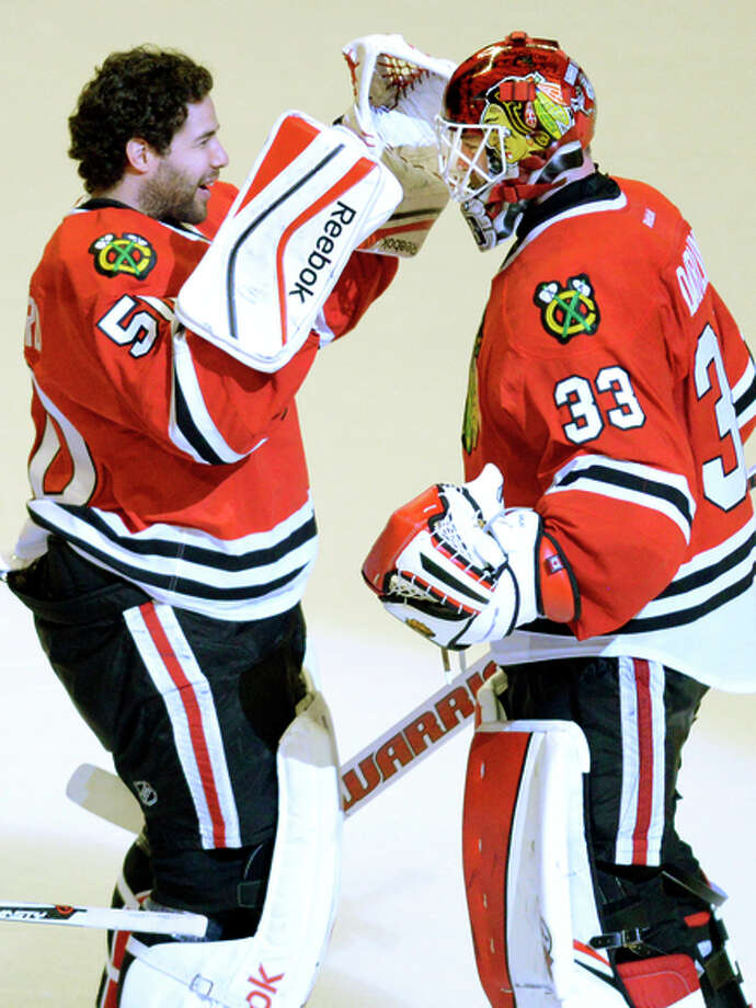 Blackhawks starting goalie Scott Darling (right) is congratulated on his 35-save victory by Corey Crawford. Photo: John Starks / Associated Press / Daily Herald