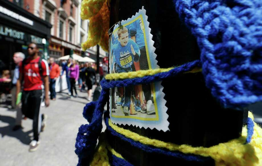 Pedestrians pass a photograph of Boston Marathon bombing victim Martin Richard, Saturday, April 18, 2015, in Boston, at the spot where the second bomb detonated at the marathon in 2013. The 119th Boston Marathon will be run on Monday. (AP Photo/Michael Dwyer) ORG XMIT: MAMD113 Photo: Michael Dwyer / AP