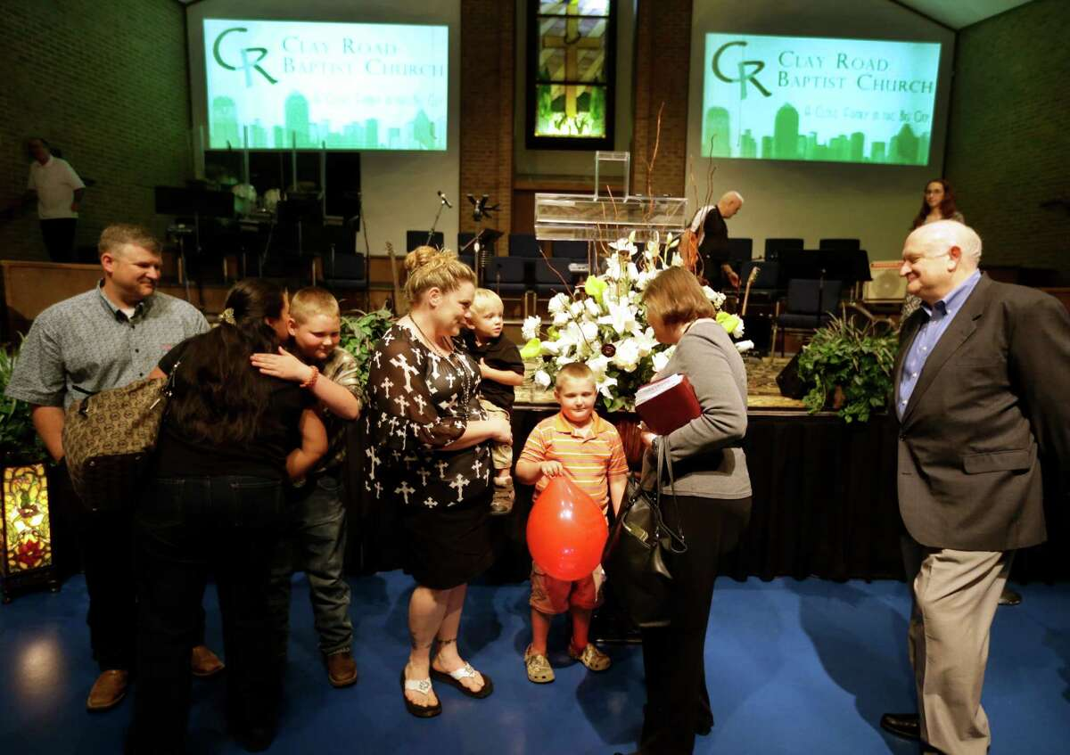 Members of the congregation line up after the Sunday service on April 12 at Clay Road Baptist Church to say goodbye as the Long family moves away from the area.