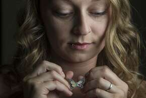 Portrait of Melissa Silva holds her mother, Deanna Butterfield pendant at her home in Tucson, Az., on Saturday April 19, 2015. Melissa Silva, was only 4 years old when her mother, Deanna Butterfield, 21, was found sexually assaulted and strangled to death at Tilden Park in the Berkeley hills in 1987. Now, William ÒWild BillÓ Huff has been charged with killing Butterfield and a second woman in San Pablo in 1993.