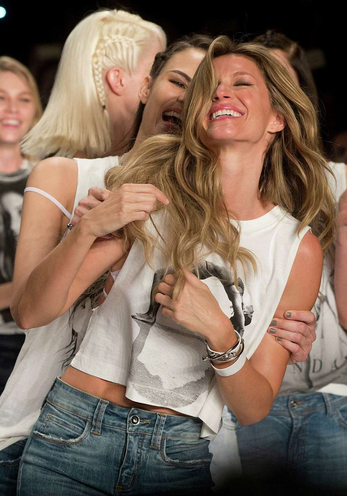 In this Wednesday, April 15, 2015 photo, Brazilian super model Gisele Bundchen celebrates with fellow Brazilian model Fernanda Tavares at the end of the show from the Colcci Summer collection at Sao Paulo Fashion Week in Sao Paulo, Brazil. Bundchen, the Brazilian supermodel who has lit up catwalks around the world for 20 years, retired from the runway.