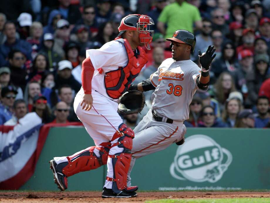 Baltimore Orioles' Jimmy Paredes, right, scores on a three-run double by teammate Adam Jones as Boston Red Sox catcher Sandy Leon, left, waits for the ball in the sixth inning of a baseball game Sunday, April 19, 2015, in Boston. (AP Photo/Steven Senne) ORG XMIT: MASR107 Photo: Steven Senne / AP