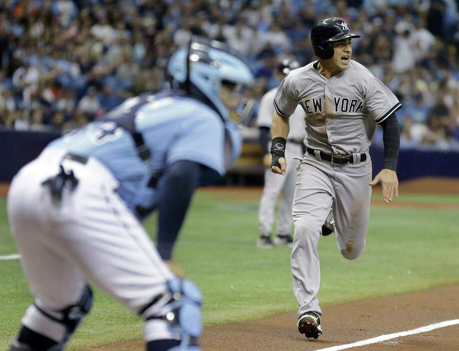 New York Yankees' Jacoby Ellsbury, right, races home to score on a sacrifice fly by teammate Mark Teixeira off Tampa Bay Rays starting pitcher Matt Andriese during the first inning of a baseball game Sunday, April 19, 2015, in St. Petersburg, Fla. Rays catcher Rene Rivera, left, looks on. (AP Photo/Chris O'Meara)  ORG XMIT: SPD108 Photo: Chris O'Meara / AP