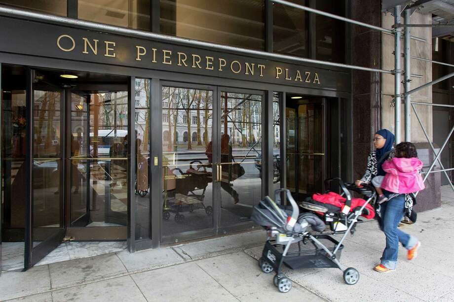 FILE- In this April 3, 2015 file photo, a woman enters One Pierrepont Plaza in the Brooklyn borough of New York. The 19-story office building rises unassumingly from downtown Brooklyn, its upper floors offering generous views of the nearby Manhattan skyline and the East River's famed bridges. Inside, the headquarters of what will arguably be the most scrutinized presidential campaign in history, Hillary Clinton's second bid at the White House. (AP Photo/Mark Lennihan, File) ORG XMIT: NYR401 Photo: Mark Lennihan / AP