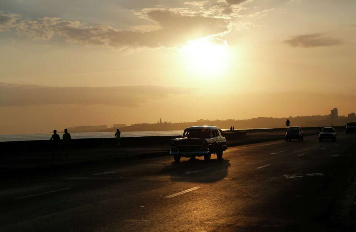 A taxi driver steers his classic American car along the Malecon at sunrise in Havana, Cuba, Wednesday, April 15, 2015. Cuban officials and ordinary citizens alike hailed the island's removal from the U.S. list of state sponsors of terrorism, saying the move by President Barack Obama heals a decades-old insult to national pride and clears the way to swiftly restore diplomatic relations. (AP Photo/Desmond Boylan) ORG XMIT: XDB101