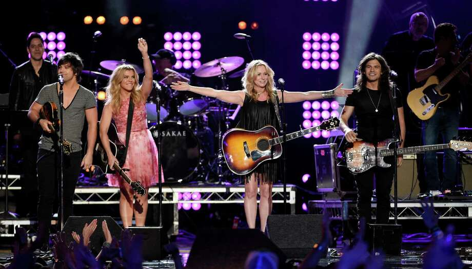"""Singer Deana Carter, second from right, performs with The Band Perry members, left to right, Neil Perry, Kimberly Perry and Reid Perry at """"ACM Presents: Superstar Duets"""" at Globe Life Park on Saturday, April 18, 2015, in Arlington, Texas. (Photo by Chris Pizzello/Invision/AP) ORG XMIT: TXCP115 Photo: Chris Pizzello / Invision"""