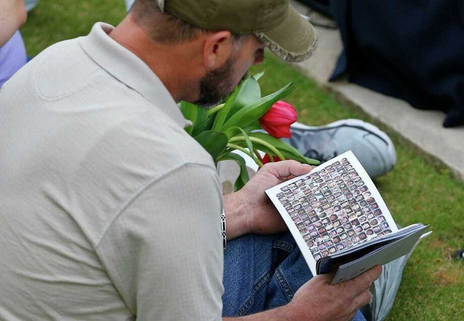 A spectator looks at a booklet containing photos of the Oklahoma City bombing victims during a ceremony to commemorate the 20th anniversary of the Oklahoma City bombing at the Oklahoma City National Memorial in Oklahoma City, Sunday, April 19, 2015. (AP Photo/Sue Ogrocki) ORG XMIT: OKSO105 Photo: Sue Ogrocki / AP