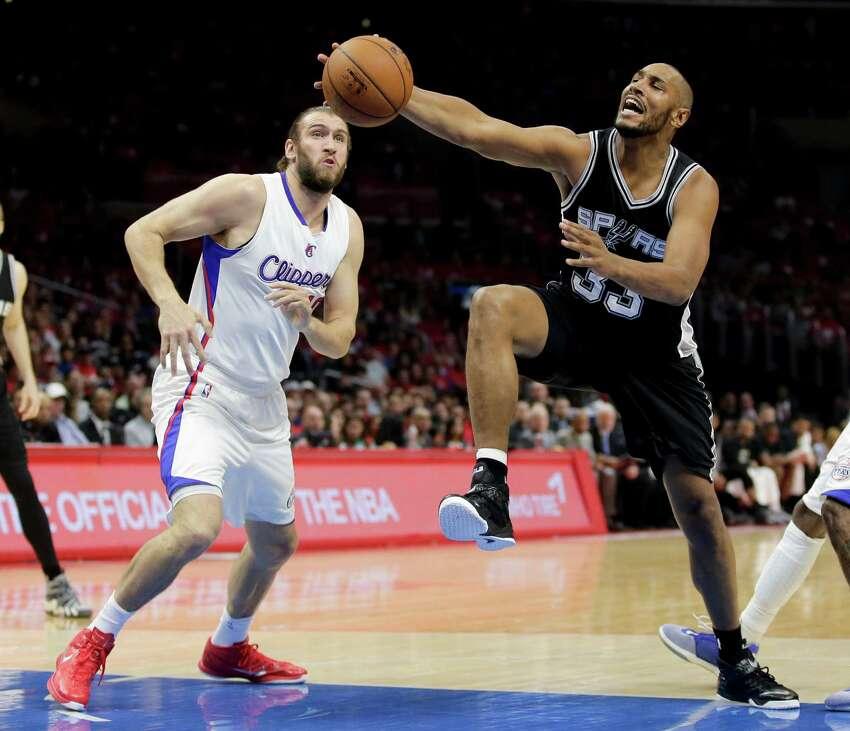 San Antonio Spurs center Boris Diaw, right, goes to the baske past Los Angeles Clippers forward Spencer Hawes during the first half of Game 1 of a first-round NBA basketball playoff series in Los Angeles, Sunday, April 19, 2015.