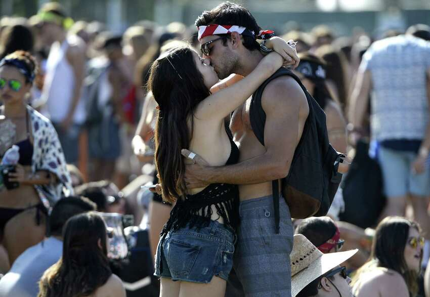 A couple kiss on the second day of the Coachella Music Festival in Indio, California on April 11, 2015. AFP PHOTO / ROBYN BECK