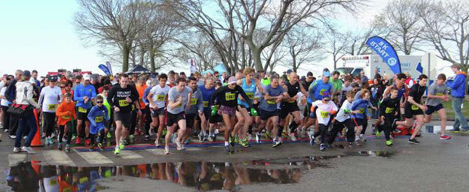 And they're off: The field of runners hits the course at last year's Minute Man Race, sponsored by the Westport Young Woman's League. This year's race and related events -- the 37th annual -- take place Sunday at Compo Beach. Photo: File Photo / Westport News