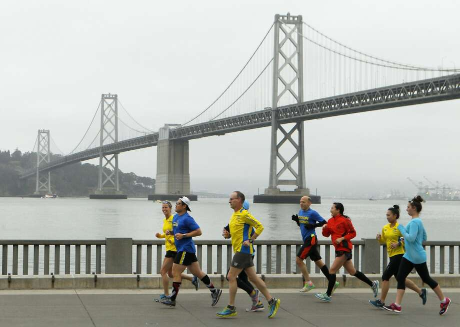 Ethan Veneklasen, third from left, and runners jog along Embarcadero, Monday, April 20, 2015, in San Francisco, Calif. More than a dozen ran from the Ferry Building along Embarcadero for a 5K run in solidarity with the Boston Marathon and those impacted by the attack two years ago. Veneklasen, from Pleasant Hill, said he finished the 2013 Boston Marathon an hour before the incident. He was at a restaurant a few blocks away when the bombs went off. Photo: Santiago Mejia, The Chronicle