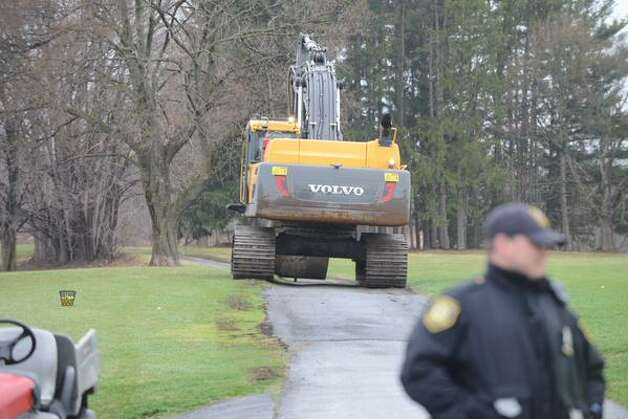Work crews and and equipment gather at Capital Hills Golf Course in Albany to tackle a mudslide along Normans Kill that is causing water to back up to the west. (Will Waldron / Times Union)