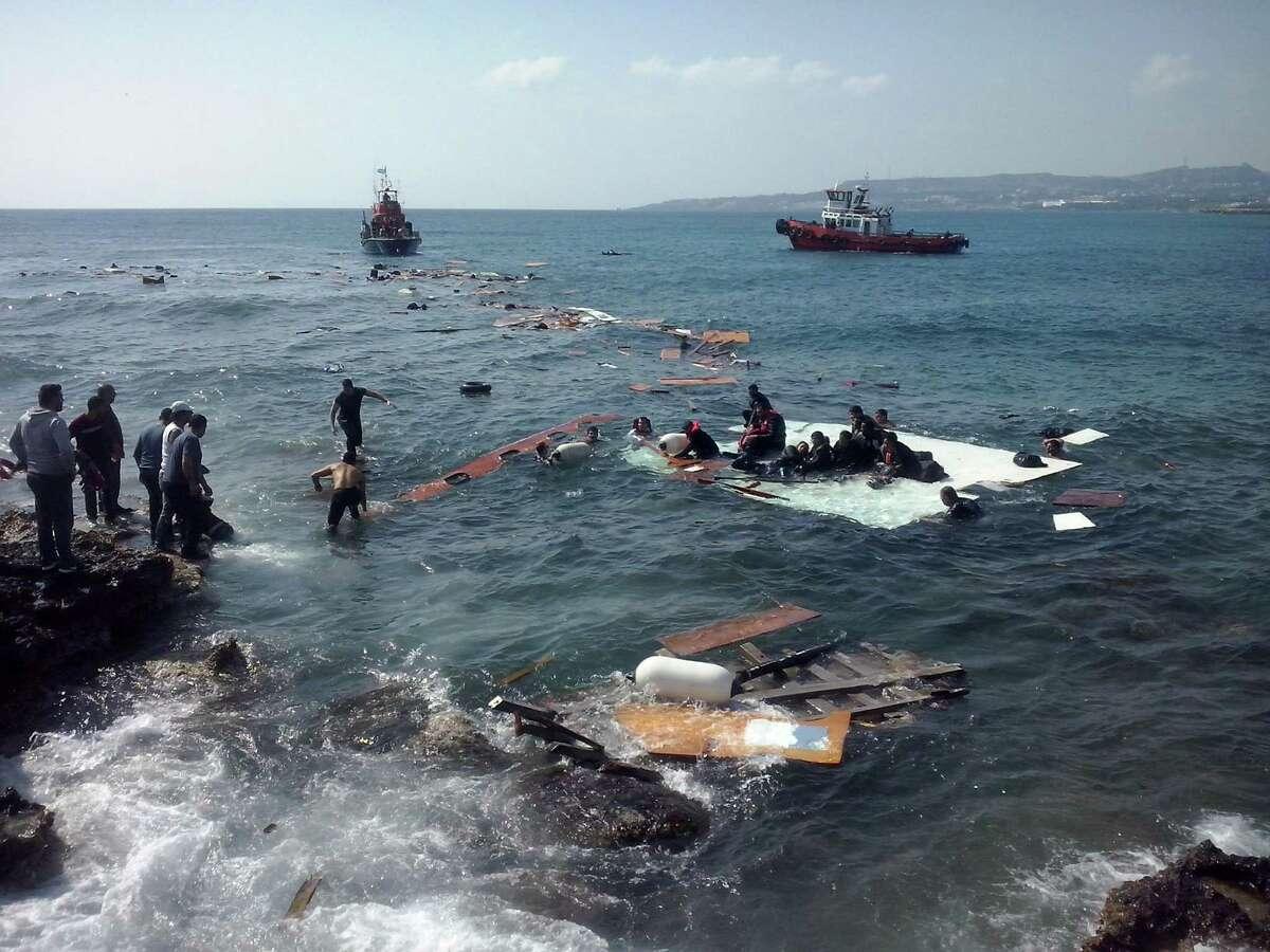 Men help survivors of a vessel that sank off the Greek island of Rhodes. Three people were feared dead.