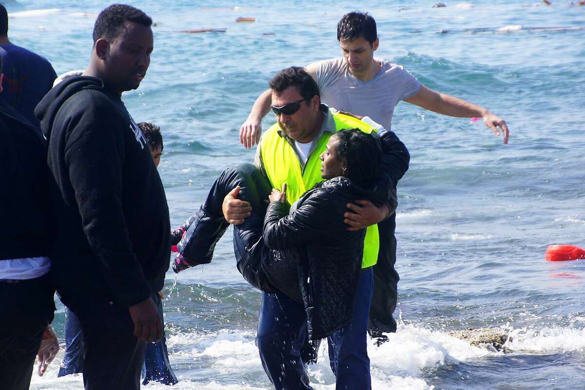 A man rescues a migrant from the Aegean sea, in the eastern island of Rhodes, Monday, April 20, 2015. Greek authorities said that at least three people have died, including a child, after a wooden boat carrying tens of migrants ran aground off the island of Rhodes. (Argiris Mantikos/Eurokinissi via AP) GREECE OUT