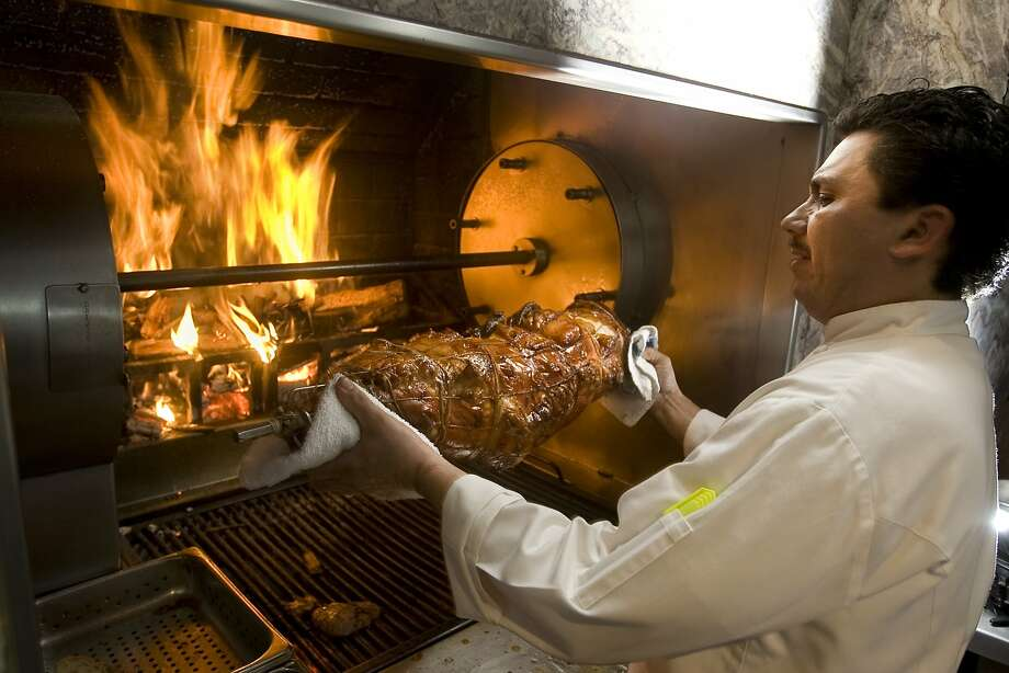 Ruben Santos, sous chef at Poggio restaurant, placing a small pig stuffed with herbed sausage into the wood burning rotisserie in Sausalito, Calif., on March 9, 2009. Photo: Craig Lee, The Chronicle