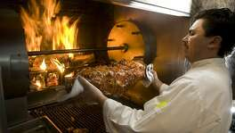 Ruben Santos, sous chef at Poggio restaurant, placing a small pig stuffed with herbed sausage into the wood burning rotisserie in Sausalito, Calif., on March 9, 2009.