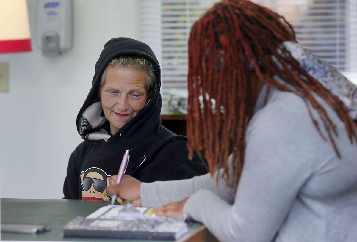Elizabeth Stromer, a homeless woman, sat down to fill out paperwork after being taken to the navigation center from her encampment Monday April 20, 2015. A homeless encampment near the corner of 16th Street and Shotwell in San Francisco, Calif. was dismantled and the people moved to the new navigation center a few blocks away.