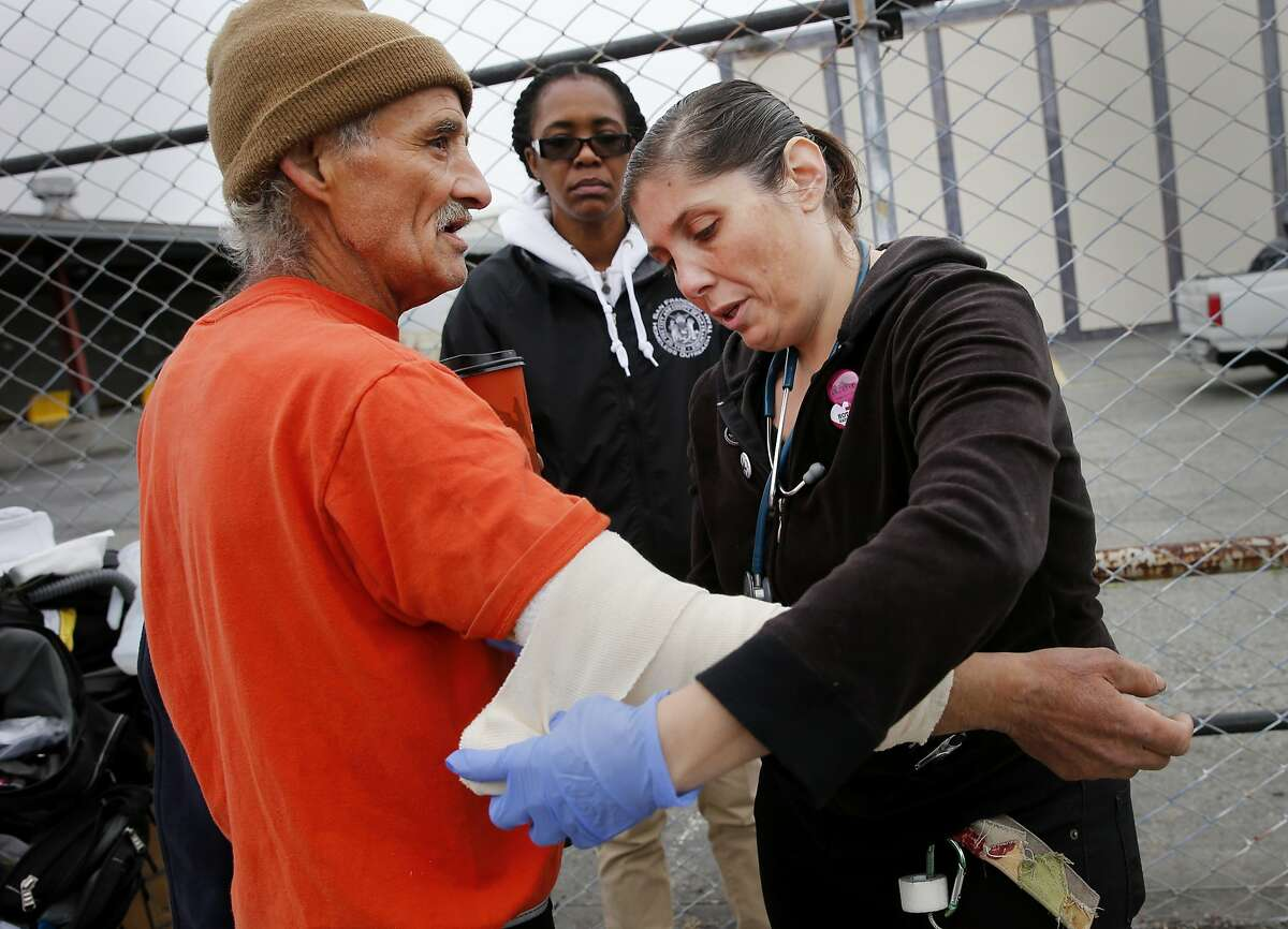 Nurse Gina Limon (right) of the Hot team changed a bandage for Marco who recently suffered a stab wound. A homeless encampment near the corner of 16th Street and Shotwell in San Francisco, Calif. was dismantled and the people moved to the new navigation center a few blocks away.