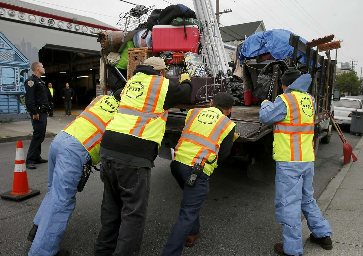 DPW crews loaded the belongings of the homeless onto a truck to be taken to the navigation center Monday April 20, 2015. A homeless encampment near the corner of 16th Street and Shotwell in San Francisco, Calif. was dismantled and the people moved to the new navigation center a few blocks away.
