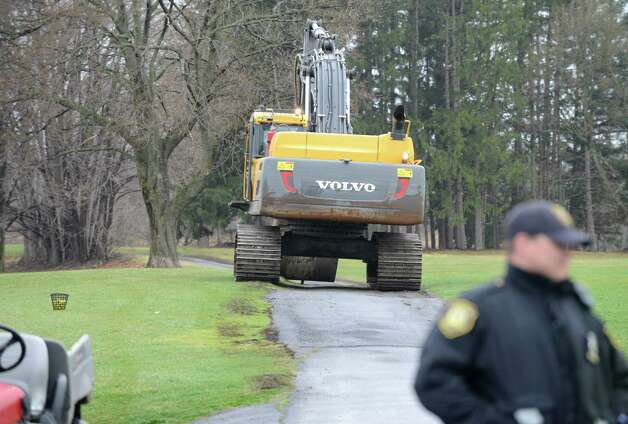 An excavator is driven into Capital Hills golf course to tackle a mudslide along Normans Kill that caused water to back up to the west Monday afternoon, April 20, 2015, in Albany, N.Y. (Will Waldron / Times Union) Photo: WW