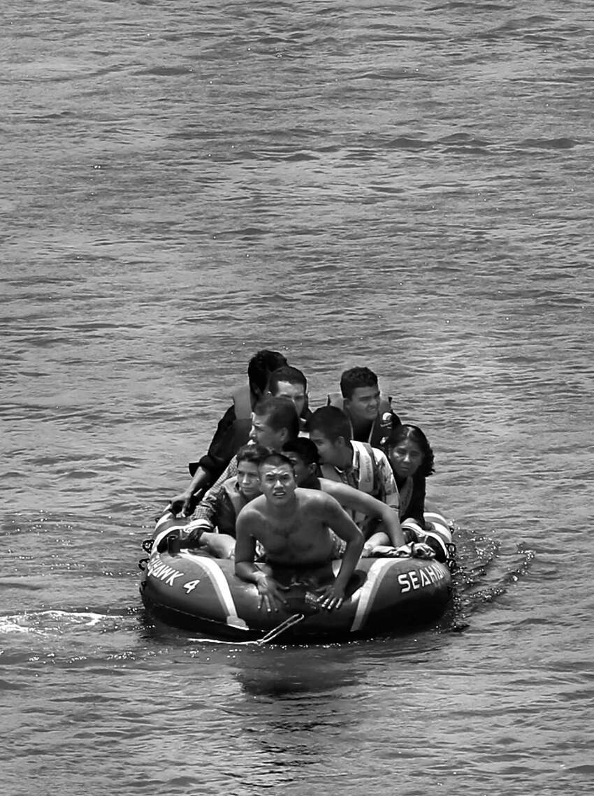Using an inflatable raft, coyotes, or smugglers, carry immigrants across by the international bridge on the Rio Grande in Roma, Tx., on June 24, 2014. According to law enforcement officials, higher risk smuggling operations have moved into Starr County in order to avoid the saturated border in Hidalgo, County.