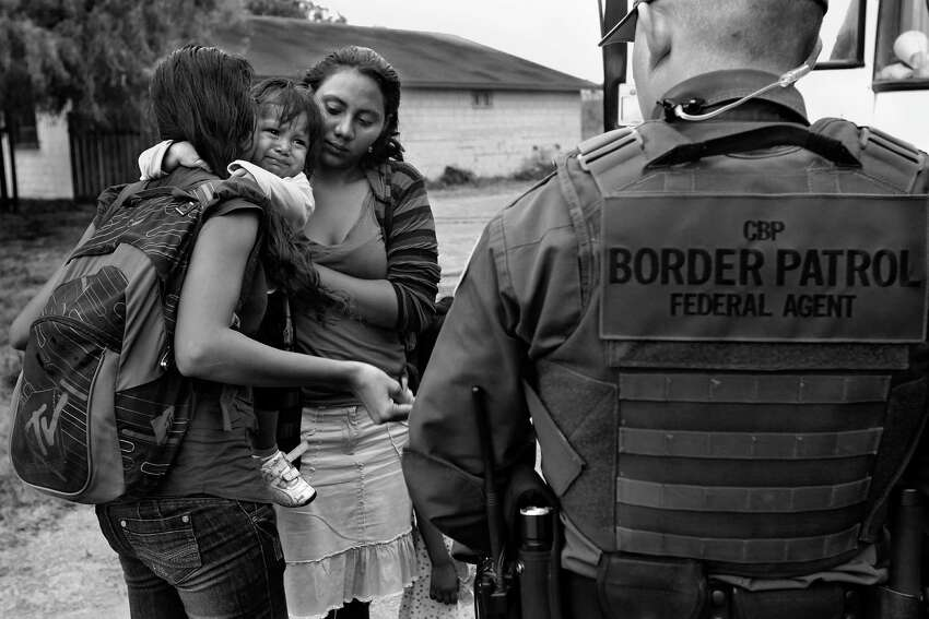 An infant cries as U.S. Border Patrol agents process a group of immigrants in Granjeno, Tx., on June 25, 2014. The city is just north of ?'El Rincon del Diablo,?