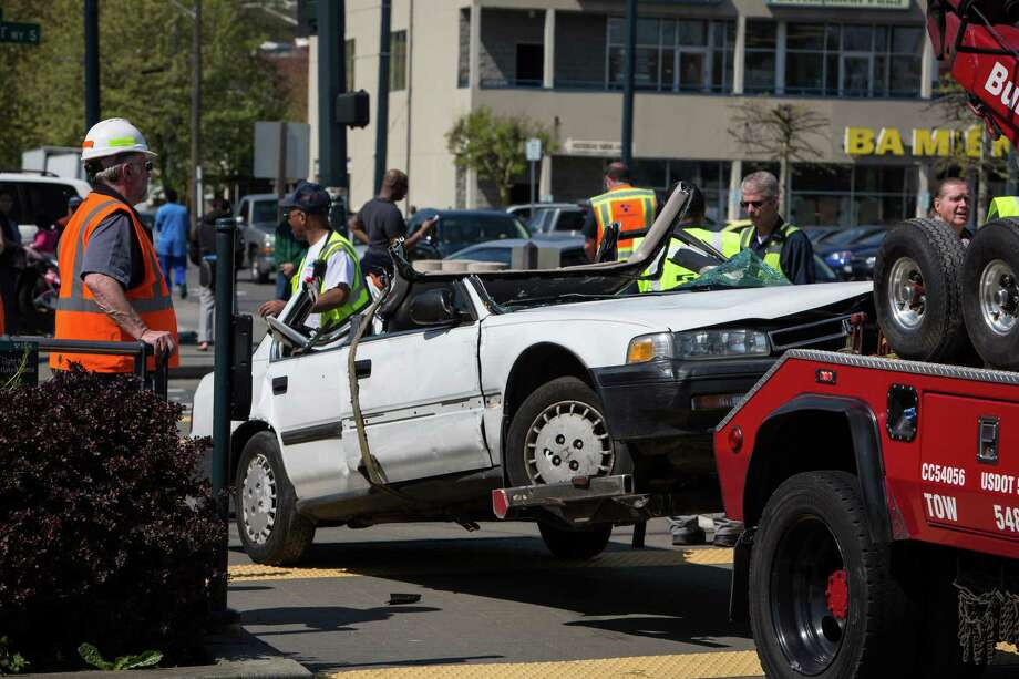 A car is towed from the center of Martin Luther King Jr. Way South after colliding with a train on Monday, April 20, 2015. The passenger in the car was pulled to safety and evaluated by medics. Photo: DANIELLA BECCARIA, SEATTLEPI.COM / SEATTLEPI.COM