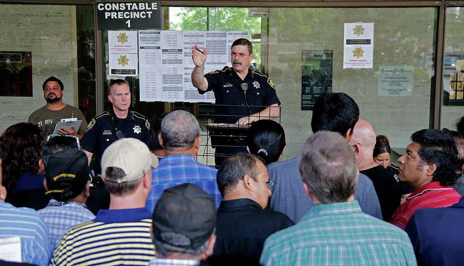 Harris County Precinct 1 Deputy Constable Richard Smith auctions off properties from Precinct 1 during the Harris County delinquent tax sale outside the Family Law Center on April 7 in Houston. Photo: James Nielsen, Houston Chronicle / © 2015  Houston Chronicle