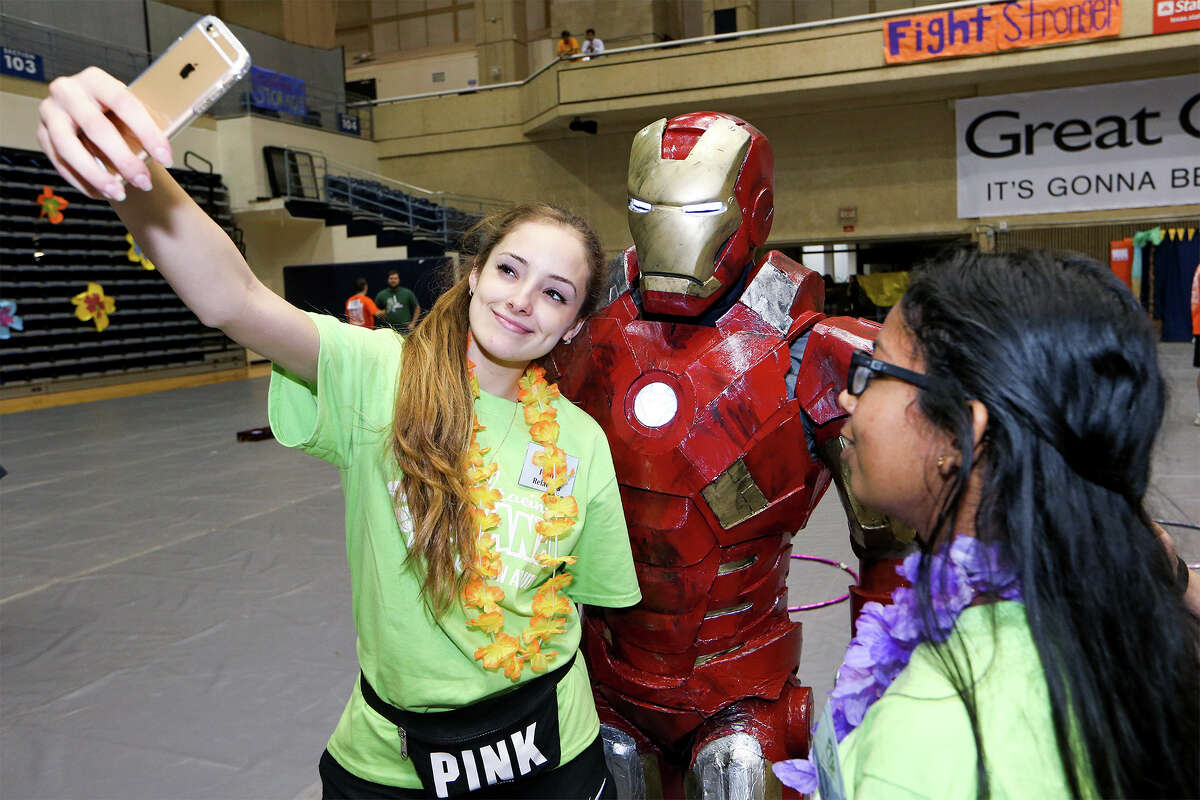 Renata Aguirre (left), 19, takes a selfie with Albert Lee in one of his Iron Man costumes as Aarthi Srinivasan, 18, looks on during a twelve hour dance marathon at the UTSA Convocation Center on Saturday, April 11, 2015. For The Kids, a UTSA student group that helps children with cancer and their families, sponsored the event. MARVIN PFEIFFER/ mpfeiffer@express-news.net