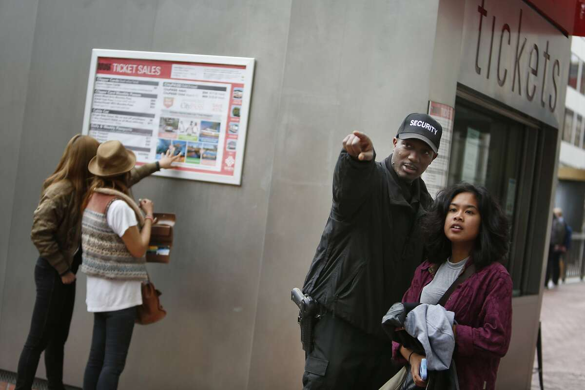 Kasayle Howard (second from right), armed security guard with Cypress Security, helps a passerby with directions while working at the cable car fare kiosk on Powell and Market Streets on Monday, April 20, 2015 in San Francisco, Calif.
