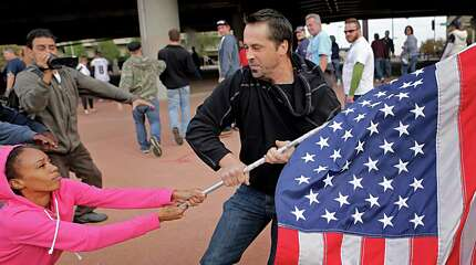 This Oct. 19,. 2014 photo by St. Louis Post Dispatch photographer David Carson shows Ferguson protester Cheyenne Green struggling to hold onto an American flag as a football fan makes a grab for it outside the Edward Jones Dome after a St. Louis Rams game. The photo staff of the St. Louis Post-Dispatch is the winner of the 2015 Pulitzer Prize for Breaking News Photography it was announced Monday, April 15, 2015, at Columbia University in New York.(David Carson/St. Louis Post-Dispatch via AP)  EDWARDSVILLE INTELLIGENCER OUT; THE ALTON TELEGRAPH OUT; MANDATORY CREDIT