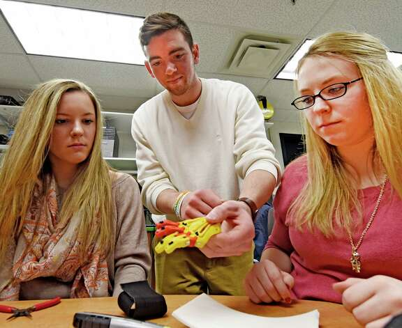 Physics majors Alyx Gleason, left, Joey Fairley, center and Miranda Marnes work on the prototype of a prosthetic hand for 5 year old Jack Carter of Columbus Ohio Monday afternoon April 20, 2015 at Siena College in Loudonville, N.Y.      (Skip Dickstein/Times Union) Photo: SKIP DICKSTEIN / 00031532A