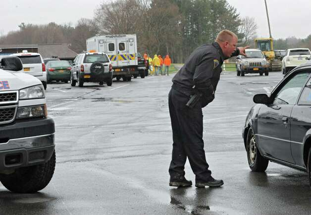 A police officer tells traffic to turn around at the Capital Hills at Albany golf course because construction crew needed to unload piping to pump out flood water due to a mudslide in the Norman Kill on Monday, April 20, 2015 in Albany, N.Y. (Lori Van Buren / Times Union) Photo: Lori Van Buren