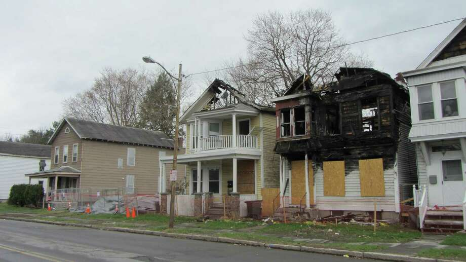 A home at 801 Second Ave. in Lansingburgh was razed by emergency order Sunday after its front and rear walls collapsed, Troy officials said. The house between 122nd and 123rd streets and the two arson-fire-damaged buildings next door are vacant. The building at 809 2nd Ave. was the scene of an arson fire in January 2015. (Bob Gardinier/Times Union)