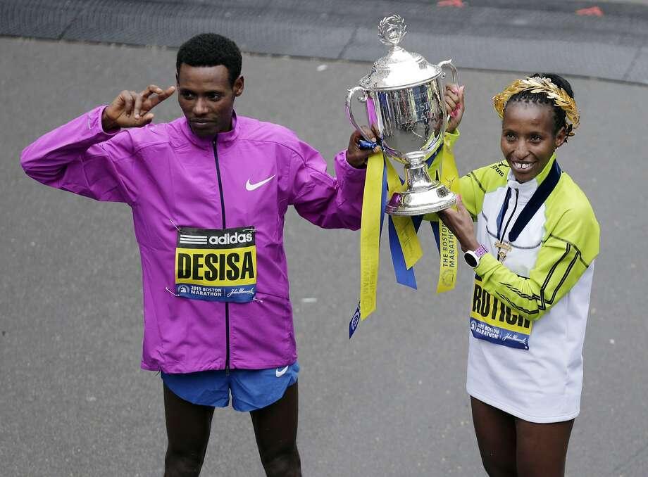 Boston Marathon winners Lelisa Desisa of Ethiopia and Caroline Rotich of Kenya hoist a trophy after the race. Photo: Charles Krupa, Associated Press