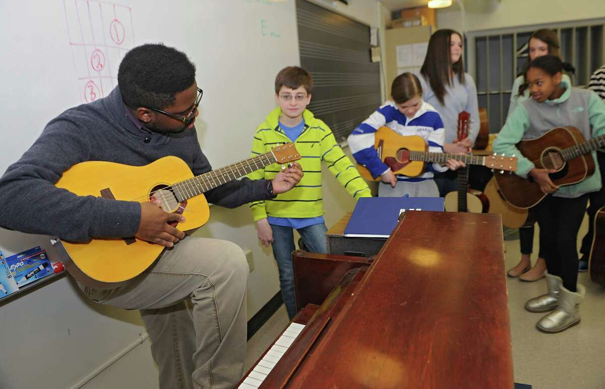 Music teacher Omar Williams helps his students tune their guitars during class at Shaker Junior High School on Monday, March 23, 2015 in Latham, N.Y. (Lori Van Buren / Times Union)