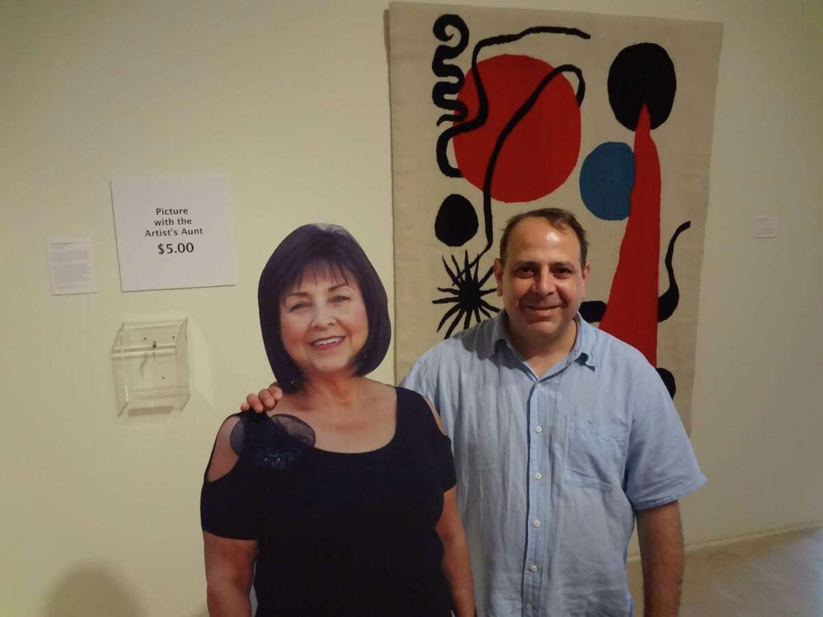 """Alejandro Diaz stands with a photo cutout of his Aunt Irene, part of piece called """"Pictures with the Artist's Aunt $5.00"""" at Space Gallery."""