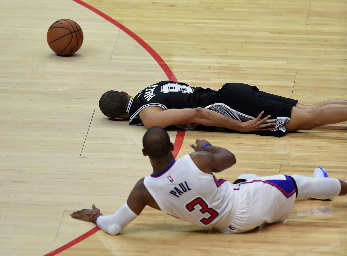 Chris Paul (3) of the Clippers and Tony Parker of the Spurs lie on the court after colliding during Game 1 at the Staples Center in Los Angeles on April 19, 2015.
