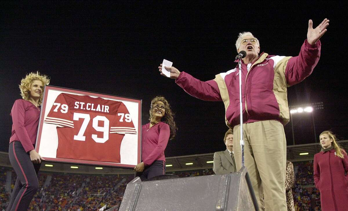 Former San Francisco 49ers tackle Bob St. Clair, right, waves to the crowd during a ceremony in San Francisco, Sunday, Dec. 2, 2001, to retire his (79) jersey when he played with the 49ers from 1953-1964. The ceremony was during halftime of the 49ers game against the Buffalo Bills. (AP Photo/Paul Sakuma)