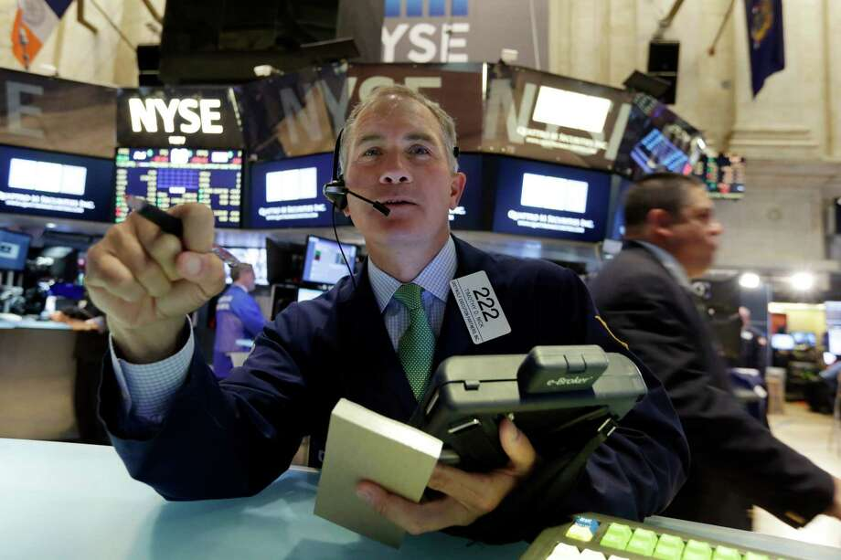 Trader Timothy Nick, left, works on the floor of the New York Stock Exchange Monday, April 20, 2015. U.S. stocks are opening higher as more big companies turn in healthy financial results for the first quarter of the year. (AP Photo/Richard Drew) ORG XMIT: NYRD103 Photo: Richard Drew / AP