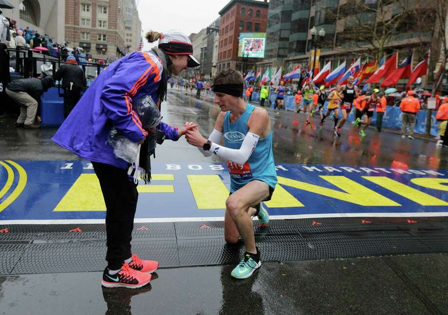 Dustin Hicks, right, of Temple Terrace, Fla., proposes marriage to Laura Bowerman after crossing the finish line of the Boston Marathon.  Photo: Elise Amendola, STF / AP