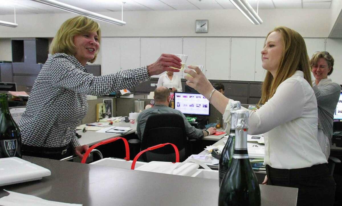 Houston Chronicle editor and executive vice president Nancy Barnes toasts Lisa Falkenberg in the newsroom.
