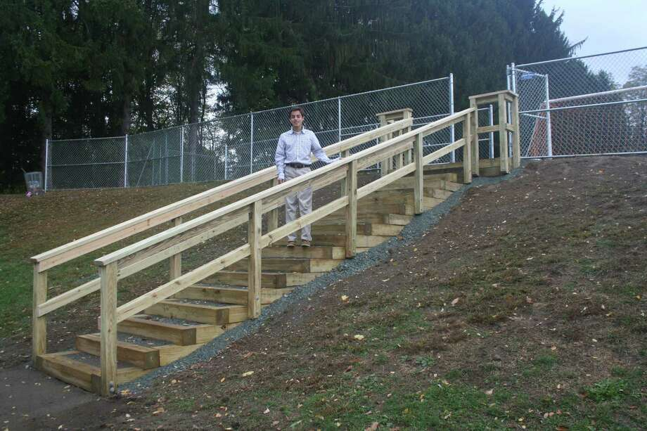 "Chris Sullivan, a Niskayuna senior, stands by the outdoor staircase leading to an athletic field at Loudonville Community Church, which was his Eagle Scout project completed in November. The project took 190 total service hours to complete. The church also functions as a school and the field is where games and practices are generally held. The previous staircase was made using only some logs and rebar, and was showing signs of wear. Sullivan worked with facilities manager Bruce Baker on the project and his uncle, a structural engineer, helped with design. He obtained the necessary supplies by going to hardware stores and asking for donations and obtained about $1,000-worth of supplies. ""I also raised money by doing a bottle and can drive throughout my neighborhood, raising another $150. It took several days to complete over the course of September through November,"" he said. ""It was certainly difficult to lead a group of people like I did when I had a limited knowledge of building and architecture, so I had to learn as I went along, and I certainly feel like I know much more than I did before the project,"" he said.He plans to attend University at Buffalo this fall and study biology to eventually become a doctor. (Submitted photo)"