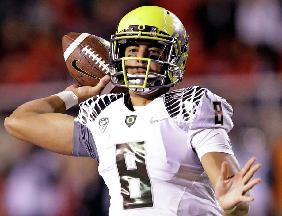 FILE - In this Nov. 8, 2014, file photo, Oregon quarterback Marcus Mariota (8) passes the ball in the second half during an NCAA college football game against Utah in Salt Lake City. When Mariota and second-seeded Oregon face Jameis Winston and third-seeded Florida State in the the College Football Playoff semifinal at the Rose Bowl on Jan. 1 it will be the third time Heisman Trophy winners have met in a postseason game. (AP Photo/Rick Bowmer, File) ORG XMIT: NY152 Photo: Rick Bowmer / AP